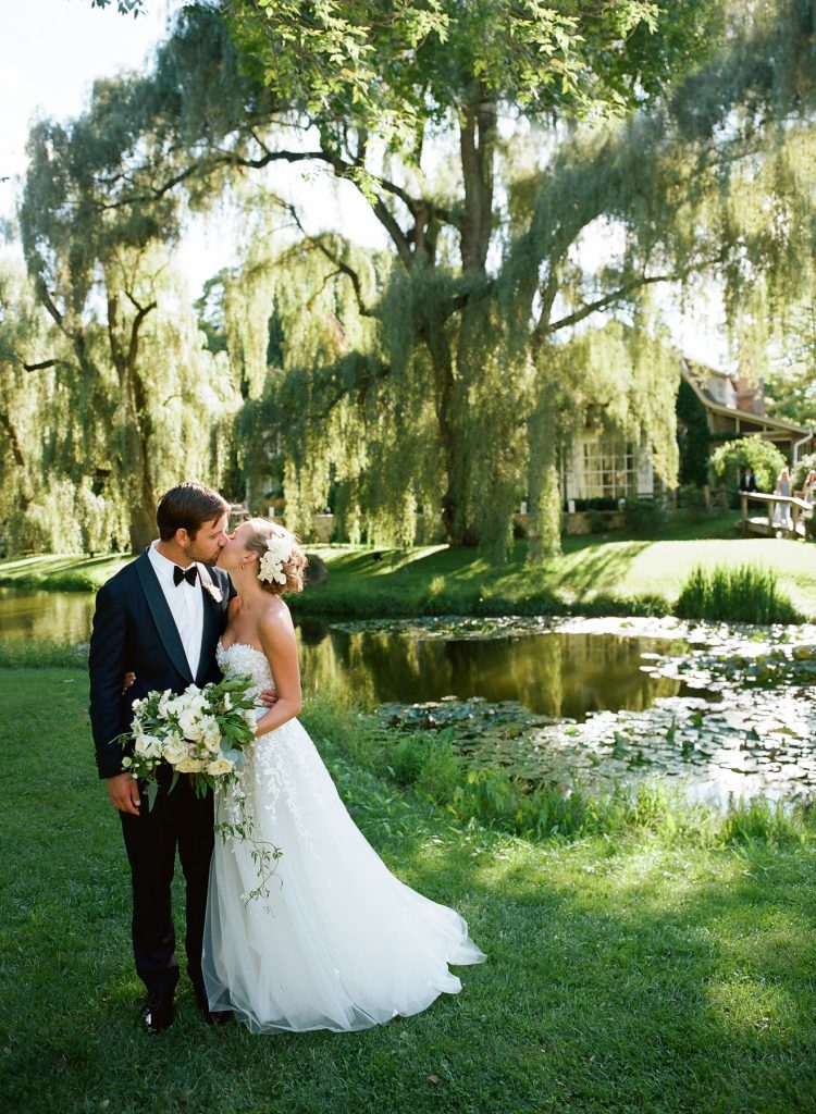 Bride and groom kissing outside near pond. Bride wears strapless Mira Zwillinger gown outdoor wedding willow tree