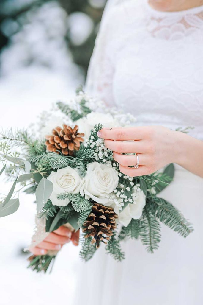 Choosing your wedding flowers for a winter wedding bouquet with pine cones and greenery