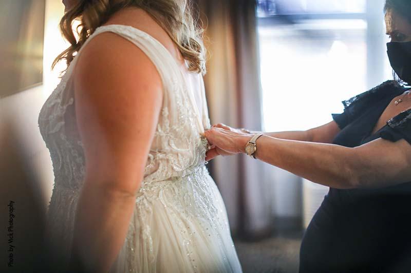 Mother helps bride zip up dress