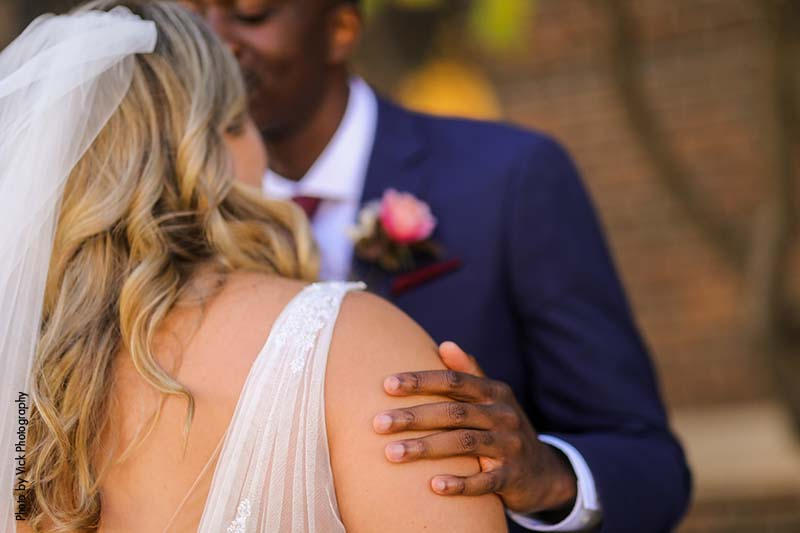 Groom puts is hand on bride's arm during first look