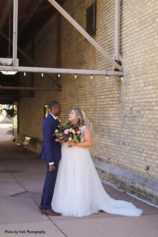 Bride and groom stand against brick in downtown Minneapolis