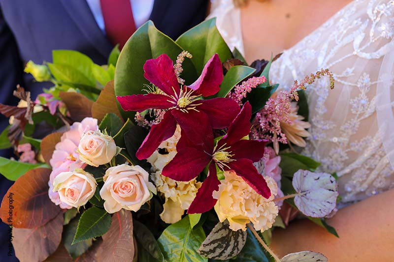 Fall bridal bouquet with maroon, pink, and white flowers and greenery