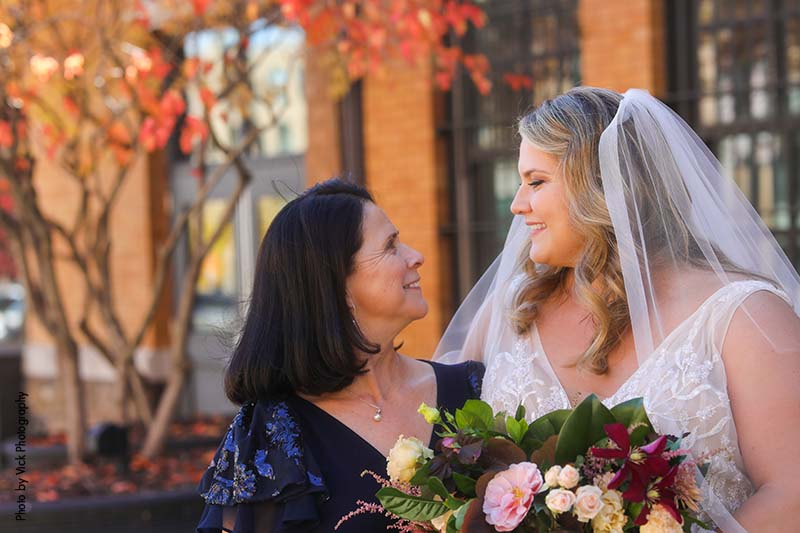 Bride in veil looks at mother of the bride in navy gown