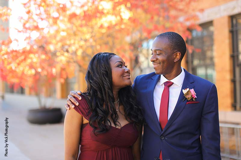 Groom in navy suit stands with bridesmaid in wine-colored gown