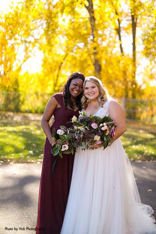Bride in ballgown poses with bridesmaid in maroon dress