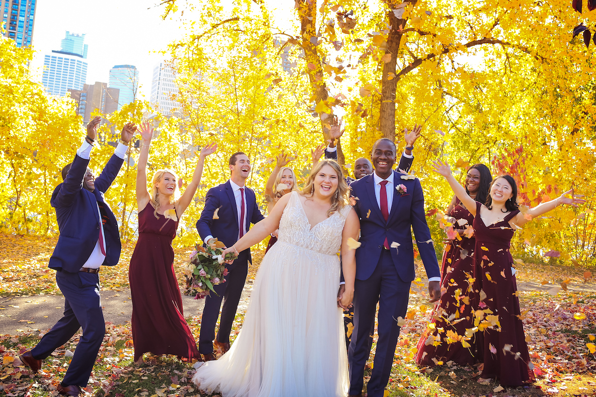 Bridesmaids in maroon dresses and groomsmen in navy suits stand by bride and groom at fall Minneapolis wedding