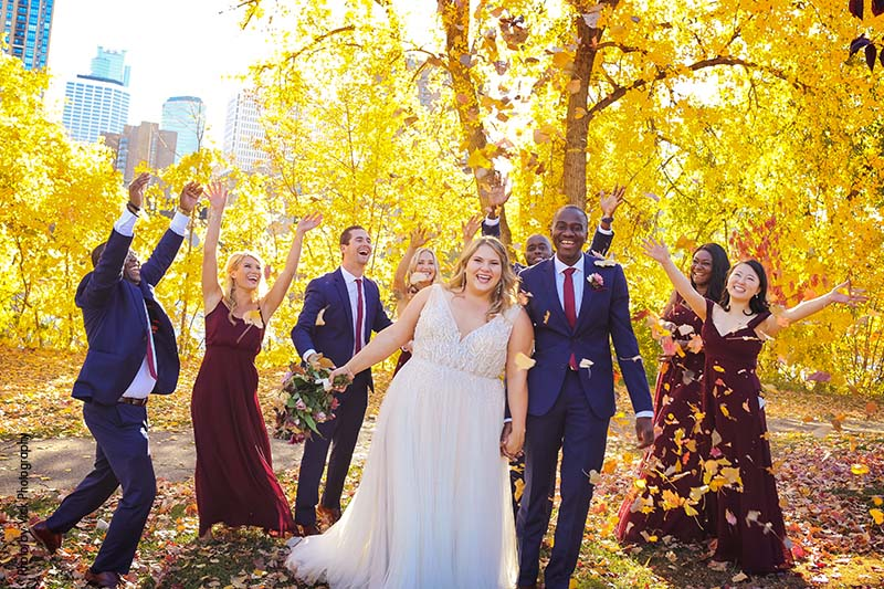 Wedding party throws leaves up in the air as they land on bride and groom