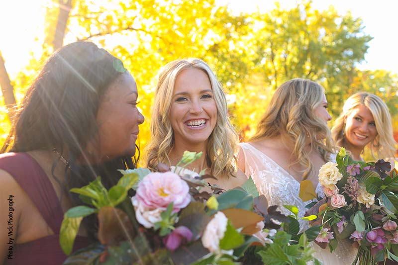 Bridesmaids in maroon gowns pose with flowers
