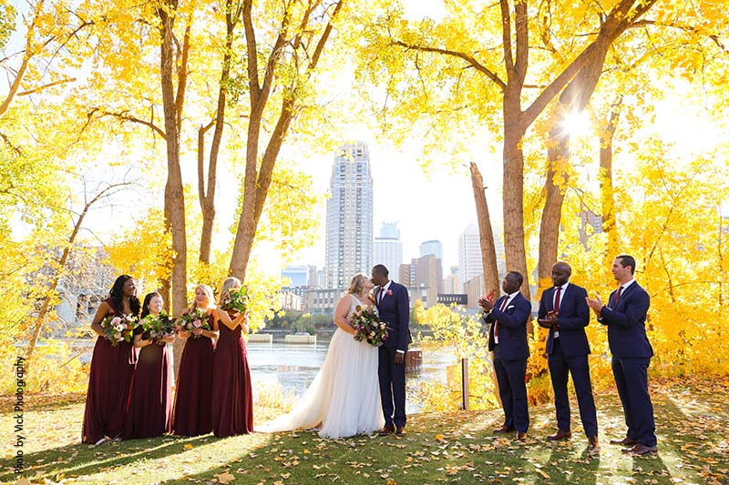 Wedding party at St. Anthony Main park between fall trees