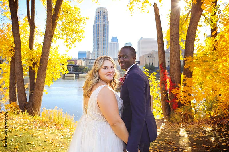 Bride and groom stand between fall trees and Minneapolis skyline