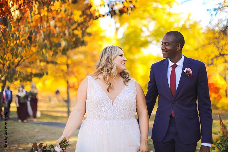 Minneapolis bride and groom walk through fall trees in a park