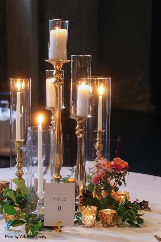 Wedding table with several taper candles and greenery