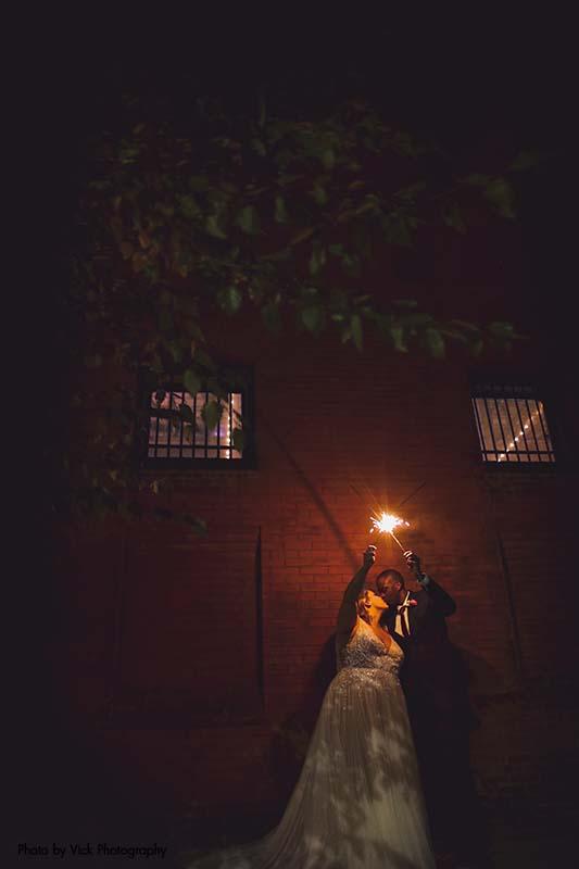 Bride and groom light a sparkler outside after wedding